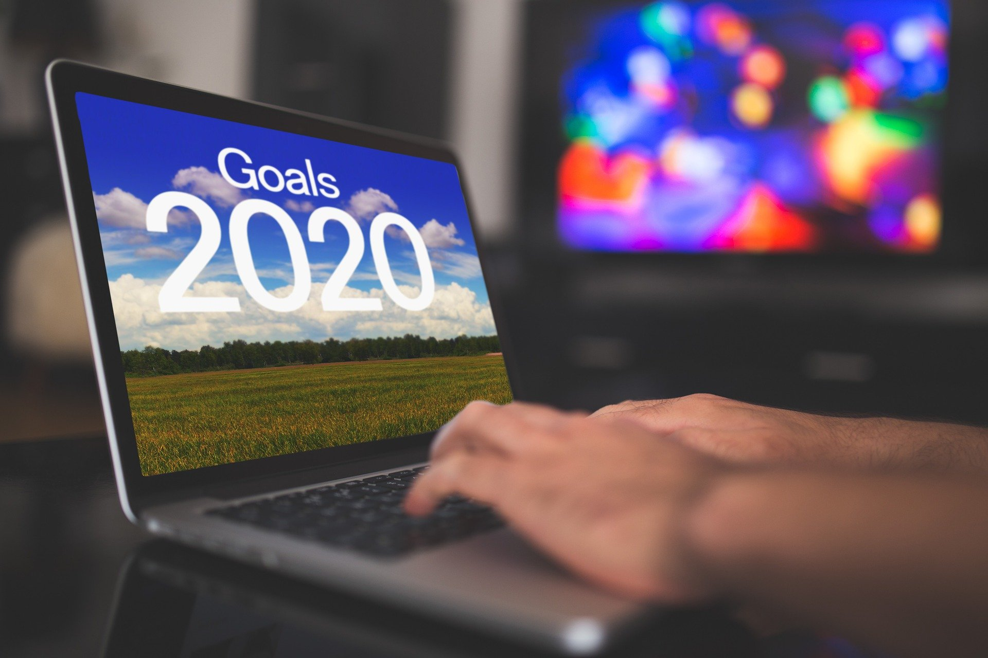 "Image of person typing on a laptop with"" Goals 2020"" on the screen"