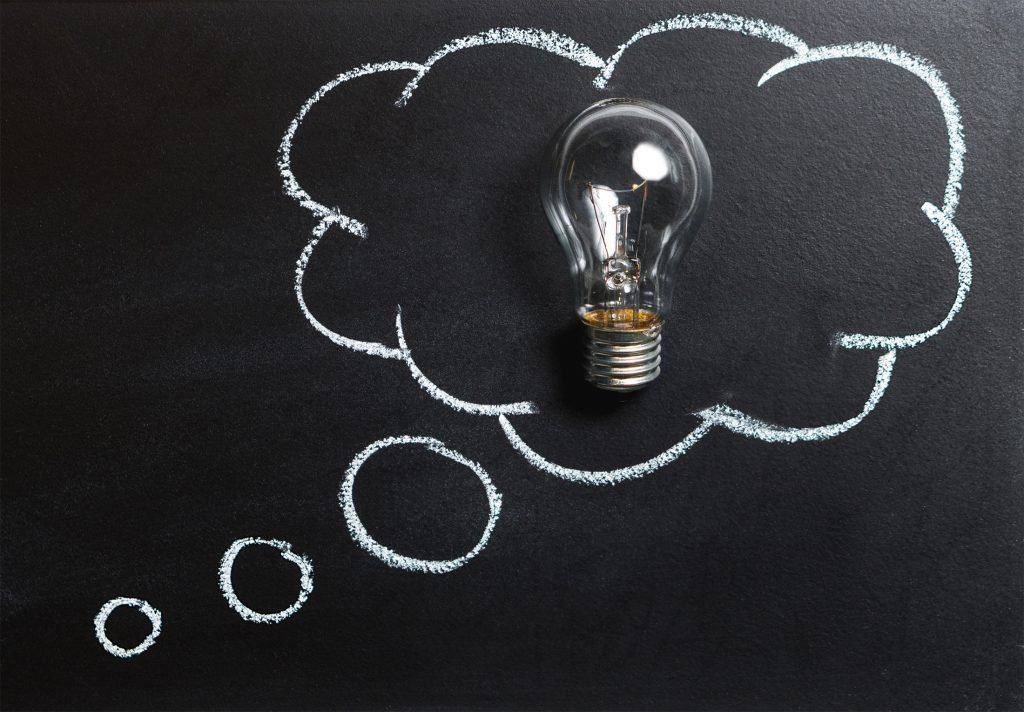 Image of a light bulb against a chalkboard surrounded by a chalk drawn thought bubble.