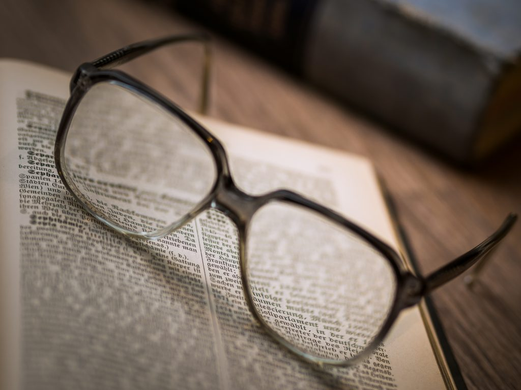 Pair of eye glasses resting on an open book page, symbolizing the wisdom of  giants our experts.
