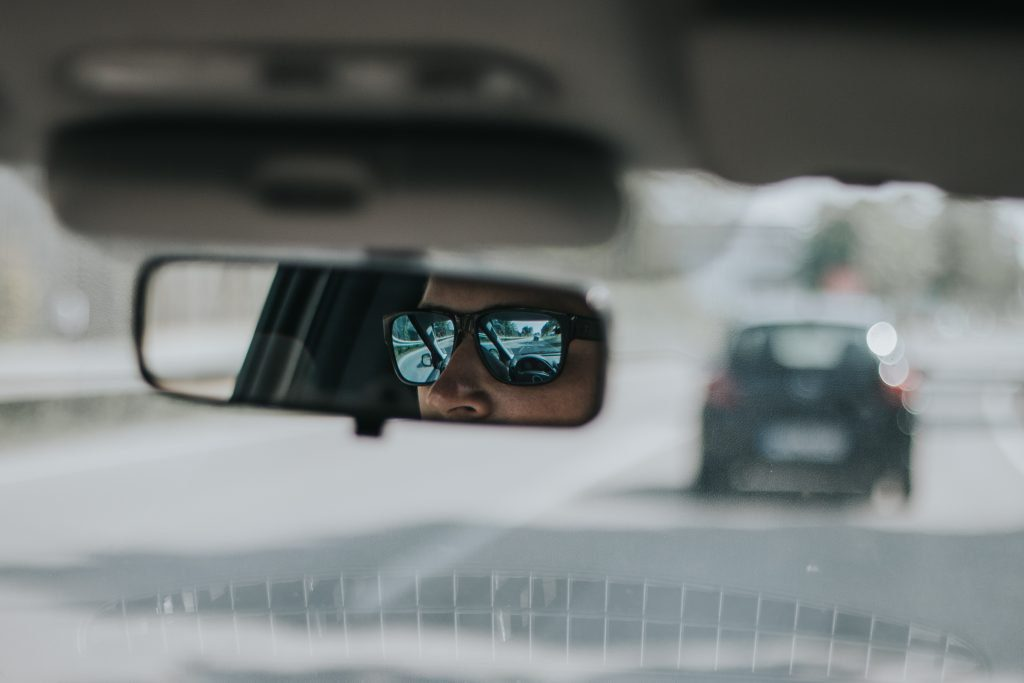 Person wearing sunglasses looking in rearview mirror