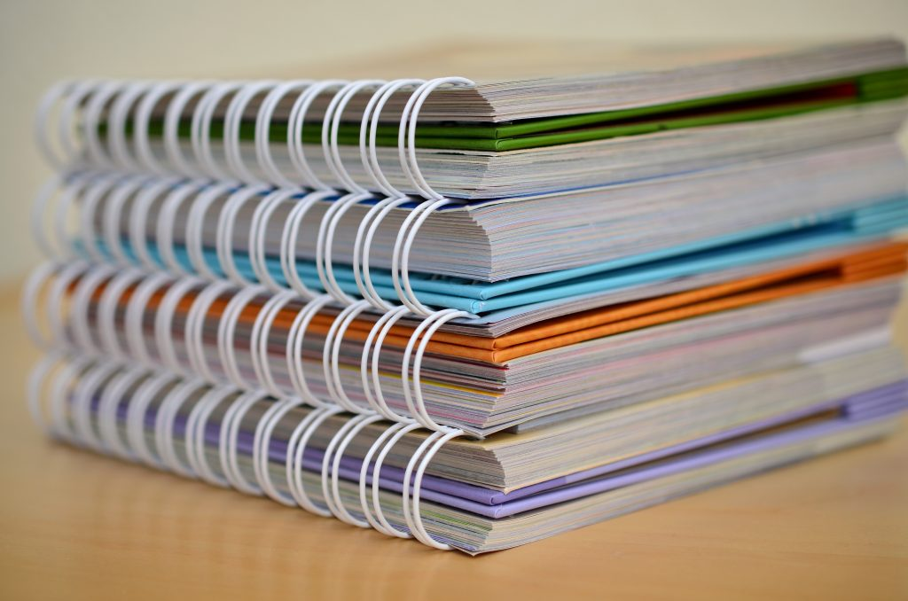 Stack of spiral notebooks representing accreditation reports.