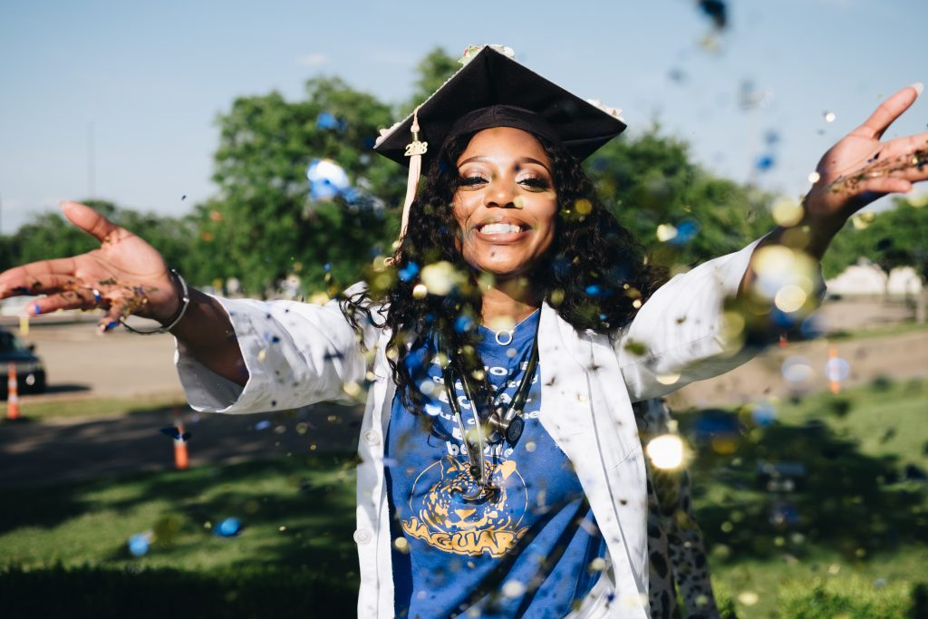 African american female college graduate throwing confetti. Effective cross-functional team management can help us improve student success!