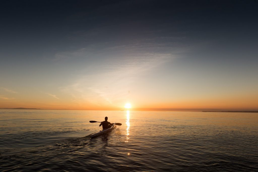 Person kayaking in the ocean into the sunset. Preparing for the accreditation process isn't a solitary affair.