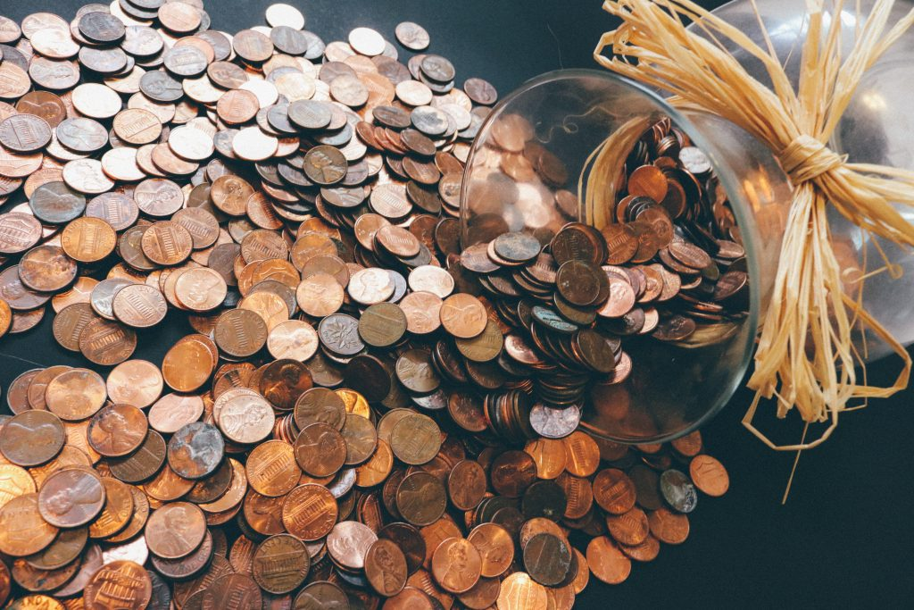 Jar of spilled pennies symbolizing money coming from talking to donors.