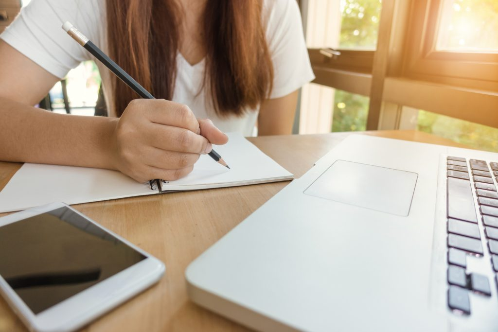 Laptop, ipad, and woman taking notes with a pencil and notebook.