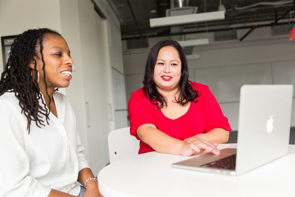 Two women looking at a laptop screen sharing information to solve a problem and becoming a data culture ambassador.