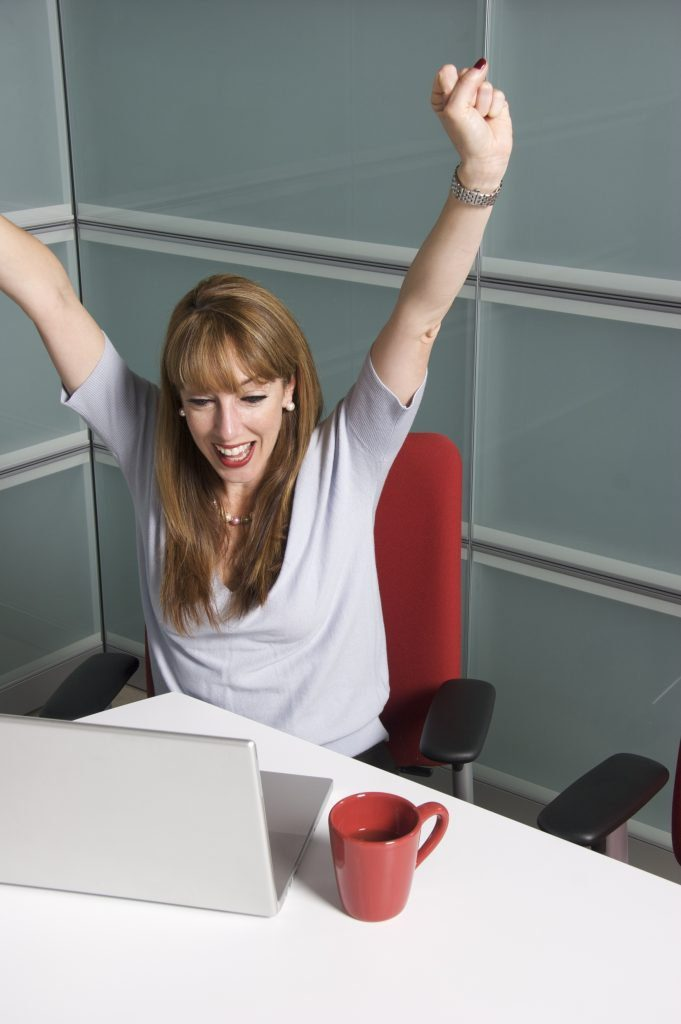 Woman sitting at a desk behind a laptop with her arms in the air in a cheer.