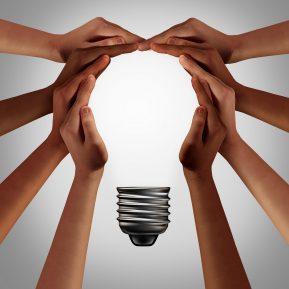 Group of hands form shape of light bulb