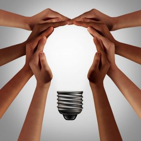 Group of hands form shape of light bulb