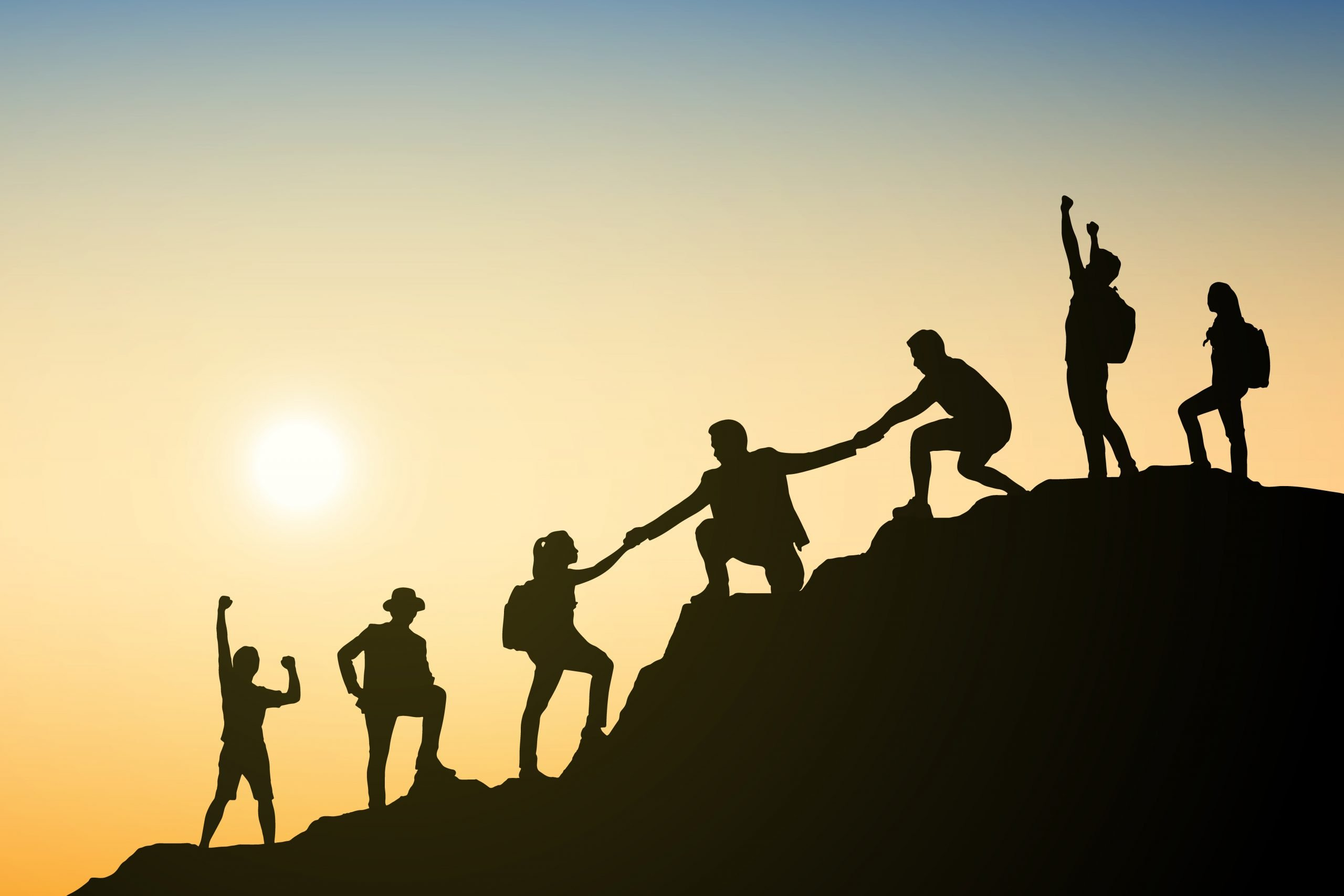 Silouette of team helping eachother climb mountain