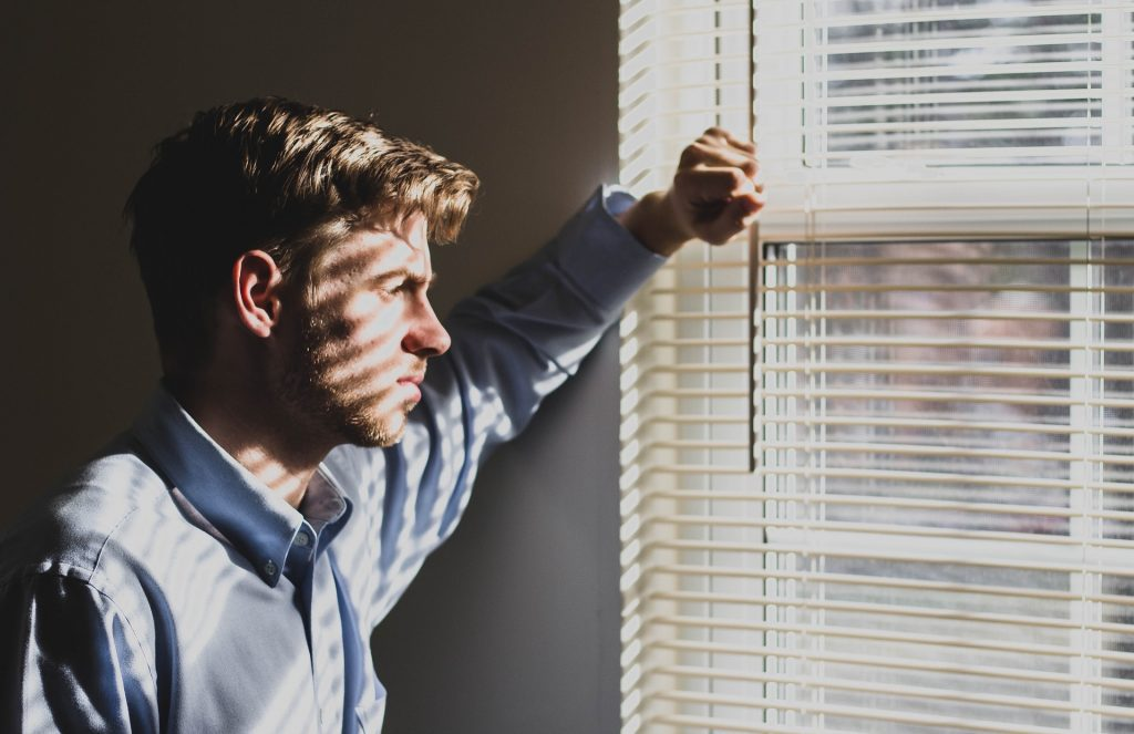 Man looking out a window with shadows of the window blinds on his face. Symbolizing the challenges of identifying and correcting Institutional Weaknesses.
