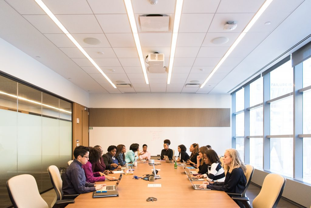 Group of diverse professionals gathered at a large conference table engaged in a meeting during challenging times.