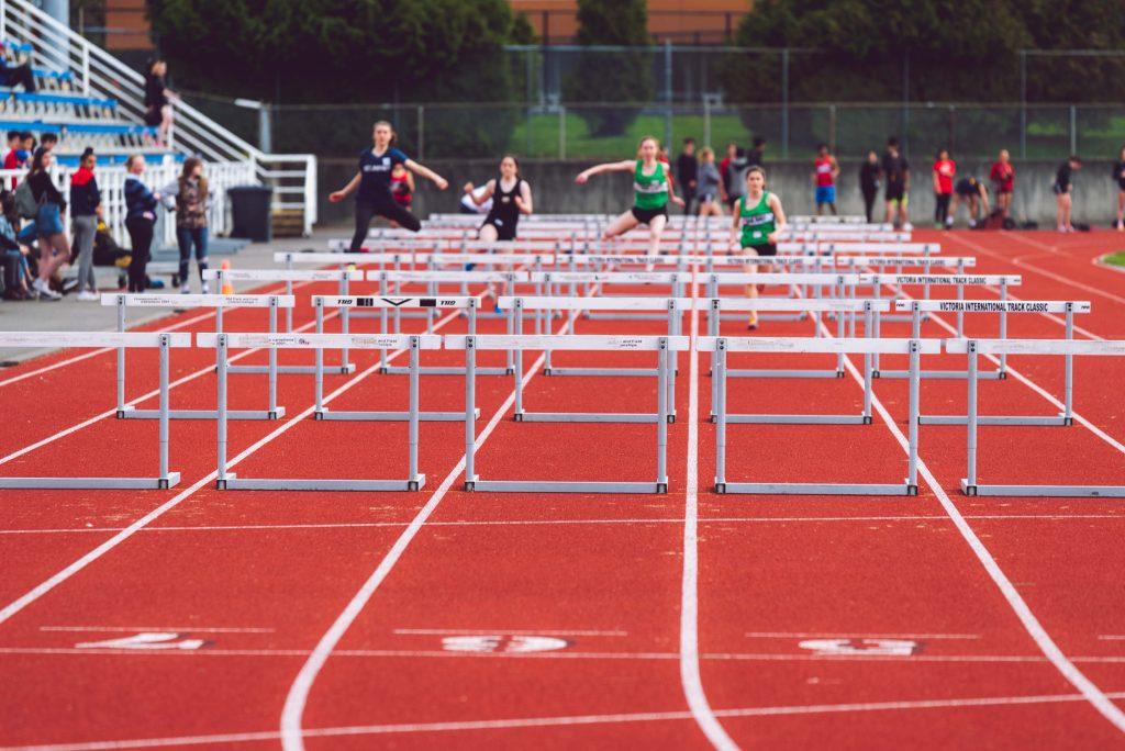 Four athletes running hurdles