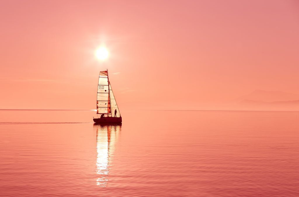 Sailboat on calm waters at  sunset. Suggesting that better times are ahead when solutions are applied to problems..