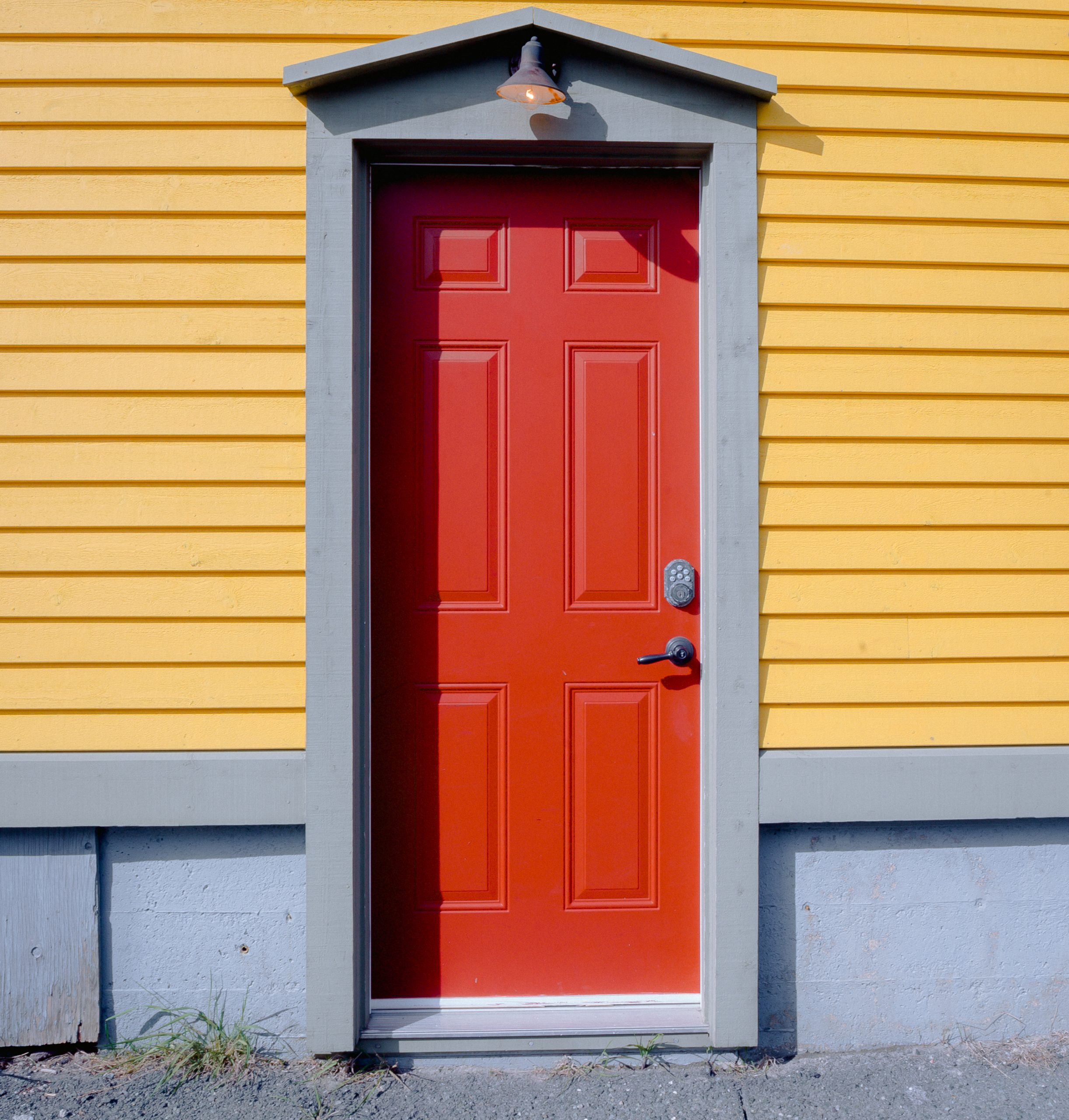 Image of a closed red door on a yellow building