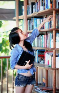 An international female student reaches for a book on a shelf. Will she be part of the Fall enrollment for 2020?