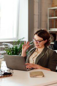 Woman conducting a college fall enrollment webinar via her laptop