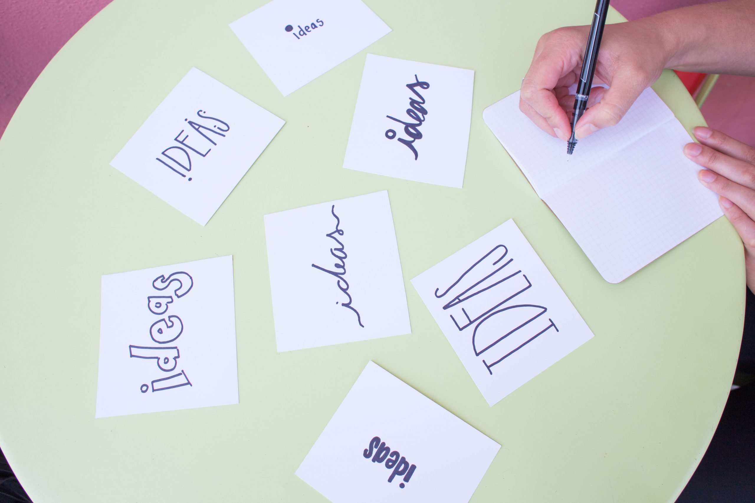Several white cards with the word Ideas scattered on a pale green table