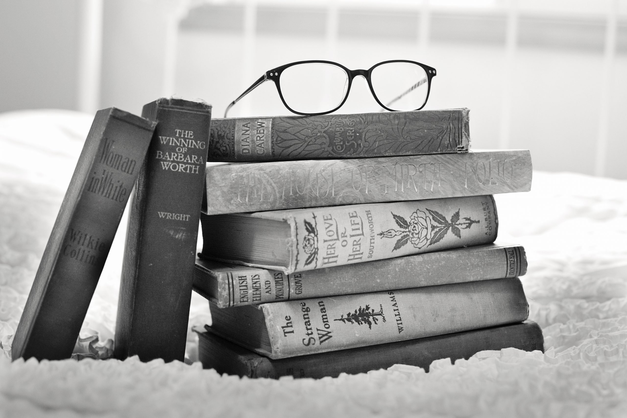 Stack of books with eyeglasses on top - symbolizing resources